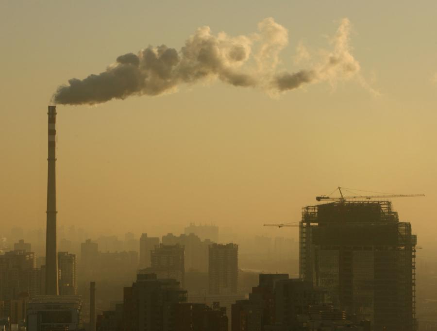 Dym unosi się z komina fabryki w dzielnicy Pekinu - Guomao