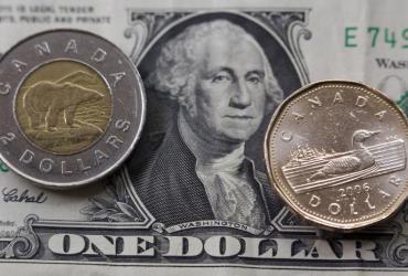Monety kanadyjskie - dwudolarowa Tooney i jednodolarowa Loonie - na tle banknotu jednego dolara amerykańskiego. Fot. Bloomberg