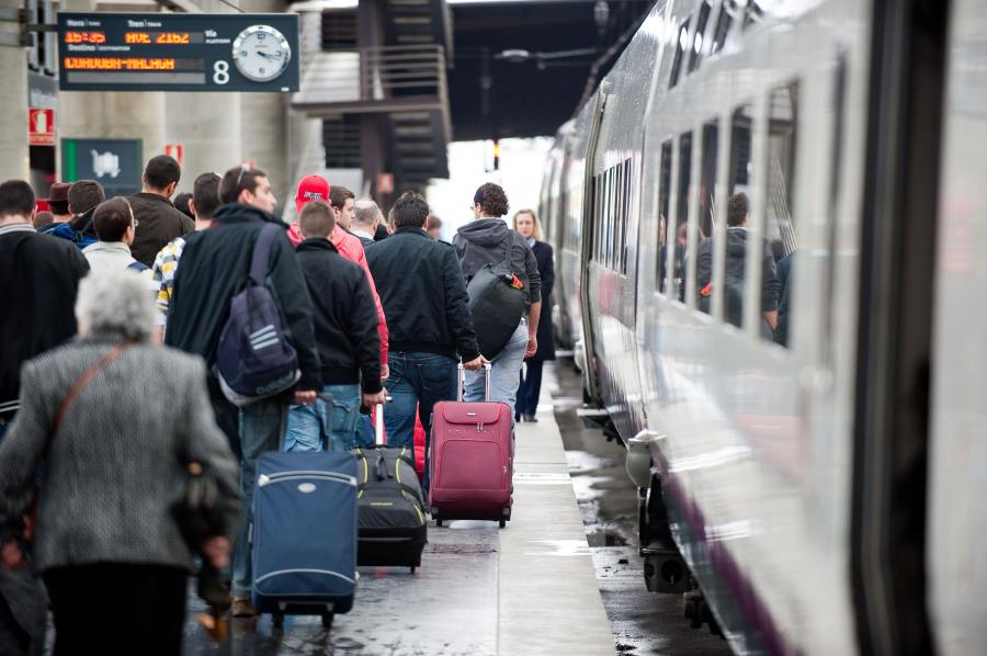 Pasażerowie wsiadający do szybkiej kolei AVE hiszpańskiej sieci kolejowej RENFE na stacji Madryt-Atocha (2). Fot. Bloomberg.