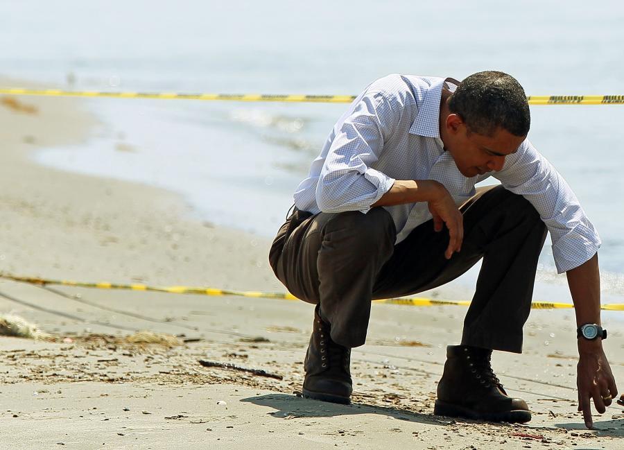 """""""Wyciekająca ropa ze zniszczonej platformy wiertniczej BP w Zatoce Meksykańskiej jest napaścią na nasze brzegi"""" – powiedział Barack Obama, komentując największą katastrofę ekologiczną w dziejach USA z 20. kwietnia 2010.  Na zdj. Prezydent Stanów Zjednoczonych Barack Obama zbiera kulki ze smoły podczas wizyty na plaży w Port Fourchon w Louisianie, 28 maja 2010."""
