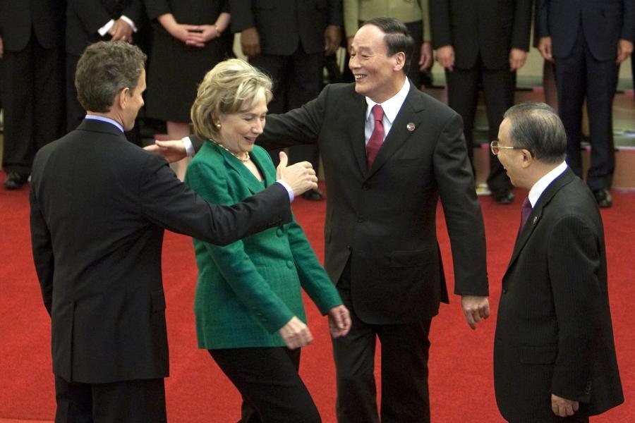 """Hilary Clinton, amerykańska sekretarz stanu """"schwytana"""" przez witających się od lewej Timothego Leithnera, amerykańskiego sekretarza skarbu oraz Wang Qishan, chińskiego wicepremiera, 24 maja 2010."""