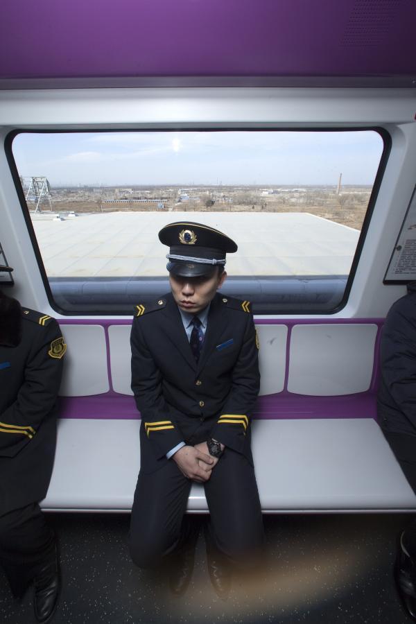 Chińskie metro: pracownik metra podróżujący nową linią metra w Pekinie