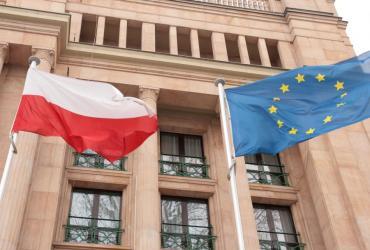 flaga polska i flaga uni europejskiej przed gmachem ministerstwa finansów