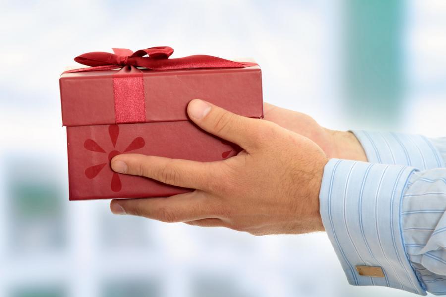 Mężczyzna wręczający prezent, mat. shutterstock