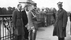 Marszałek Józef Piłsudski (środek) i generał Gustaw Orlicz-Dreszer (po prawej) na Moście Poniatowskiego w Warszawie, podczas Przewrotu Majowego 12 maja 1926 r. Źródło: 13.5 × 8.5 cm pocztówka numer #bw508918, z kolekcji starych zdjęć Dr. Marka Tuszyńskiego. Autor: Marjan Fuks (imię ze stempla na odwrocie pocztówki). Zdjęcie udostępnione w domenie publicznej.