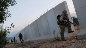 Izraelscy żołnierze kryją się za betonowym murem na granicy z Libanem w Metulah, fot. Nir Kafri/Bloomberg News