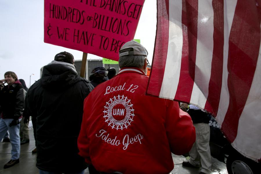Związkowiec z UAW dolącza do demonstracji przed Cobo center w Detroit.