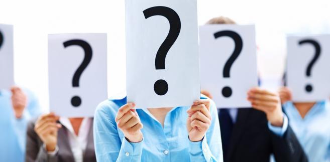 Ludzie trzymający kartki z namalowanym znakiem zapytania
