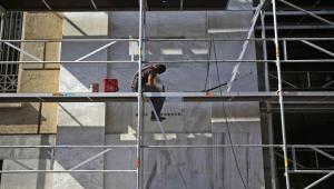 Grecja; pracownik budowlany na rusztowaniu przed budynkiem greckiego banku centralnego w Atenach
