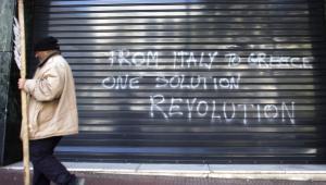 Protestujący przechodzi obok graffiti w języku angielskim Od Włoch do Grecji, jedno rozwiązanie - rewolucja na ulicach Aten, stolicy Hellady