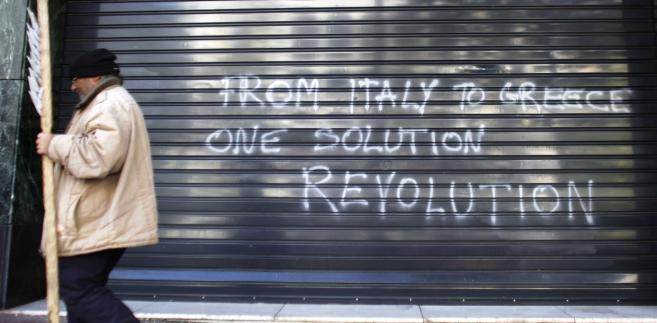 """Protestujący przechodzi obok graffiti w języku angielskim """"Od Włoch do Grecji, jedno rozwiązanie - rewolucja"""" na ulicach Aten, stolicy Hellady"""