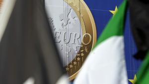 Baner z symbolem euro w tle flag przed siedzibą Komisji Europejskiej Berlaymont w Brukseli.