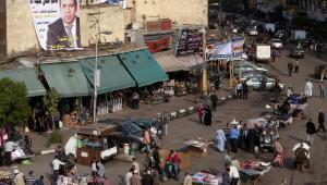 Handel uliczny w Kairze: sprzedawcy zgromadzeni pod plakatem wyborczym, Egipt, listopad 2011