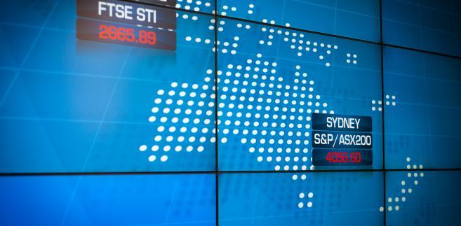 Tablica z kursami indeksów na giełdzie w Sydney, fot. Ian Waldie/Bloomberg