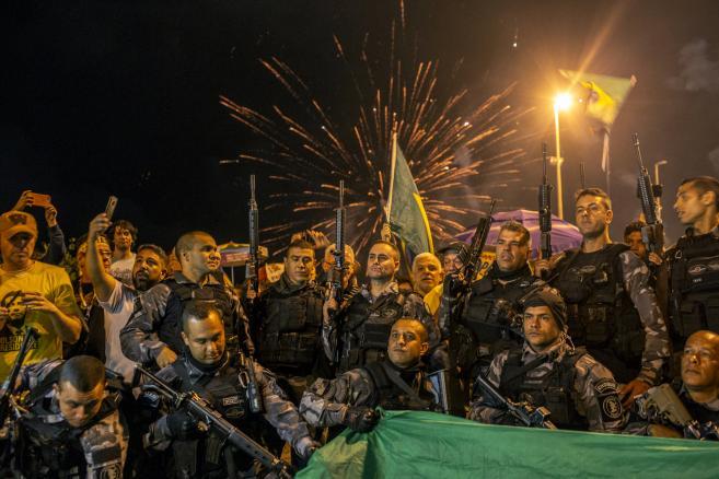 Milicja w Rio de Janeiro pozuje do zdjęcia na tle fajerwerków po ogłoszeniu wstępnych wyników drugiej tury wyborów prezydenckich w Brazylii.