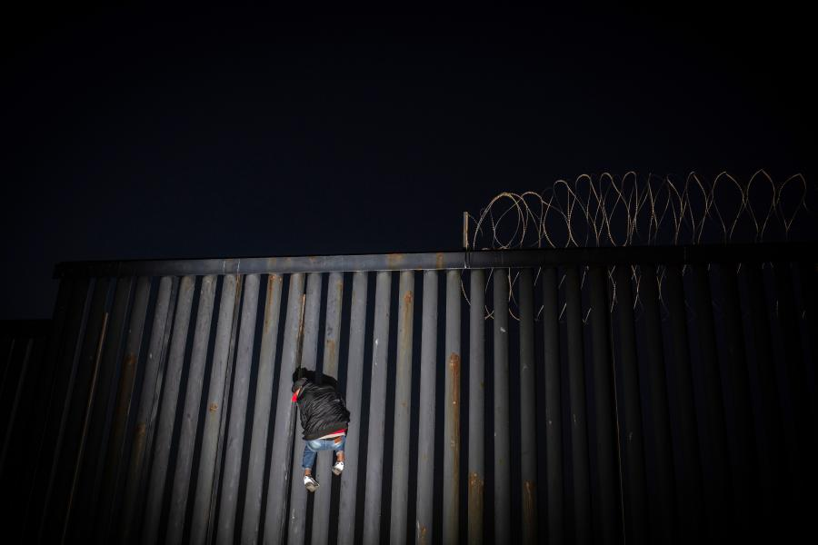 Mężczyzna wspina się po ścianie na granicy między USA a Meksykiem