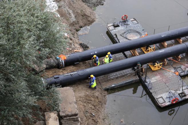 Układanie rurociągu zastępczego na moście pontonowym na Wiśle